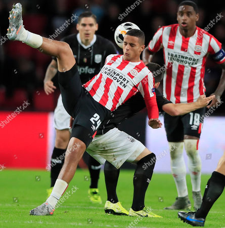 Stock Image of PSV's Mohammed Ihattaren lands on the back of LASK's Peter Michorl after jumping to head the ball during the group D Europa League soccer match between PSV and LASK at the Philips stadium in Eindhoven, Netherlands