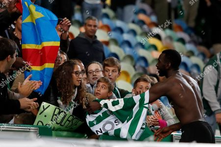 Sporting's Yannick Bolasie gives his shirt to supporters at the end of the Europa League group D soccer match between Sporting CP and Rosenborg at the Alvalade stadium in Lisbon, . Bolasie scored the goal in Sporting's 1-0 win
