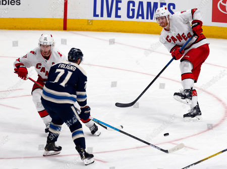 Carolina Hurricanes defenseman Dougie Hamilton, right, passes the puck in front of Columbus Blue Jackets forward Nick Foligno, center, and Hurricanes' Jordan Staal, left, during the third period of an NHL hockey game in Columbus, Ohio, . The Blue Jackets won 4-3 in overtime