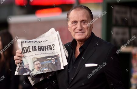 """Joe Cortese holds a prop newspaper as he arrives at the Los Angeles premiere of """"The Irishman"""", at the TCL Chinese Theatre"""