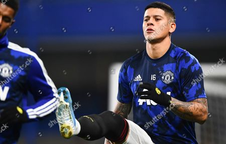 Marcos Rojo of Manchester United warms up in a t-shirt as his team mates wear multiple layers