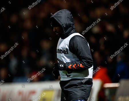 Jermain Defoe of Rangers wraps up as he warms up on the sidelines on a cold night in Dingwall.