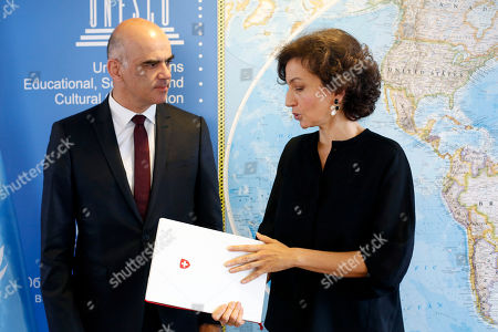 Swiss Confederation President Alain Berset, left, is welcomed by UNESCO'S Director-General Audrey Azoulay before a meeting on protection of underwater cultural héritage, at the UNESCO's headquarters in Paris