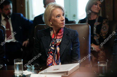 Education Secretary Betsy DeVos listens to President Donald Trump during a Cabinet meeting in the Cabinet Room of the White House in Washington. A federal judge has held DeVos in contempt of court for violating an order to stop collecting loans from thousands of former for-profit college students
