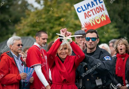 Actress and activist Jane Fonda is arrested at the Capitol for blocking the street after she and other demonstrators called on Congress for action to address climate change, in Washington, . Fellow actor Ted Danson applauds in back at center right