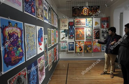 Stock Photo of Visitors observe some of the posters exhibited at the Objeto Museum, in Mexico City, Mexico, 25 October 2019. From Metallica to Juan Gabriel, through Madonna, Franz Ferdinand, Radiohead or Cafe Tacvba. These are some of the artists and bands that agreed to immortalize their concerts through screen-printed posters that today have become authentic pieces of collecting. The Museum of the Object of Mexico City presented on Friday a sample with more than 450 pieces of screen printing that explore the cross between music and graphic art through concert posters, also known as 'gig poster'.