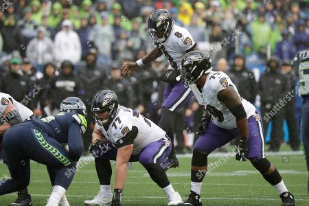 Baltimore Ravens quarterback Lamar Jackson leaps behind the line of scrimmage as Ravens' Bradley Bozeman (77) and Ronnie Stanley (79) line up against the Seattle Seahawks during the second half of an NFL football game, in Seattle