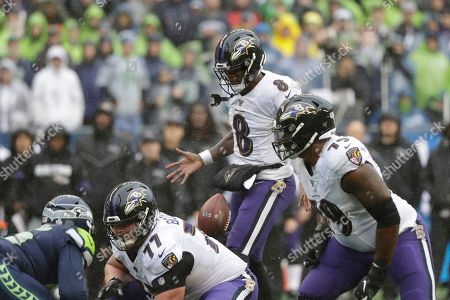 Baltimore Ravens quarterback Lamar Jackson leaps as he bobbles the snap at the line of scrimmage as Ravens' Bradley Bozeman (77) and Ronnie Stanley (79) line up against the Seattle Seahawks during the second half of an NFL football game, in Seattle
