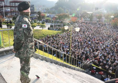 G-Dragon (L), a member of South Korean boy band BIGBANG, looks at fans who came to greet his discharge from mandatory military service at a military base in Yongin, South Korea, 26 October 2019.