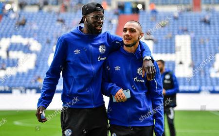 Schalke's Salif Sane, left, embraces Schalke's Ahmed Kutucu prior the German Bundesliga derby soccer match between FC Schalke 04 and Borussia Dortmund in Gelsenkirchen, Germany