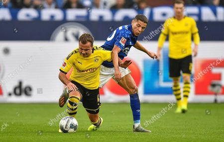 Schalke's Amine Harit, right, and Dortmund's Mario Goetze challenge for the ball during the German Bundesliga derby soccer match between FC Schalke 04 and Borussia Dortmund in Gelsenkirchen, Germany