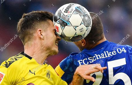 Dortmund's Julian Weigl, left, and Schalke's Amine Harit challenge for the ball during the German Bundesliga derby soccer match between FC Schalke 04 and Borussia Dortmund in Gelsenkirchen, Germany