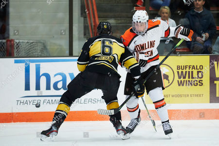 Michigan Tech defenseman Cooper Watson (6) and Bowling Green defenseman Will Cullen (2) battle for the puck during an NCAA hockey game on in Bowling Green, Ohio