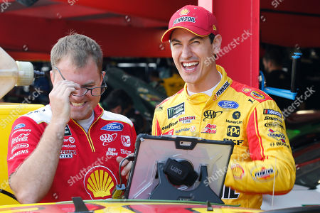 Joey Logano, right, shares a laugh with a crew member in the garage at Martinsville Speedway In Martinsville, Va., . Elliott had an engine failure less than five minutes into the opening practice for the third round of NASCAR's playoffs