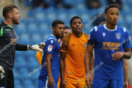 Tristan Abrahams of Newport County is marked by Brandon Comley of Colchester United ahead of a corner