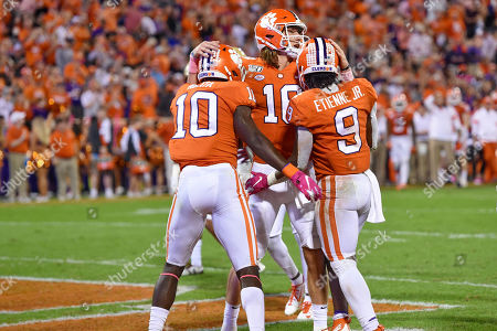 Clemson's Trevor Lawrence, back, and Joseph Ngata, left, celebrate a touchdown by Travis Etienne, right, during the first half of an NCAA college football game against Boston College, in Clemson, S.C