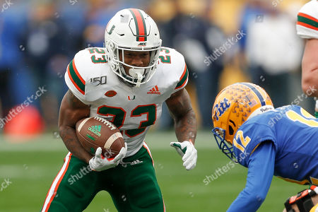 Miami running back Cam'Ron Harris (23) looks to evade Pittsburgh defensive back Paris Ford (12) during the first half of an NCAA college football game, in Pittsburgh