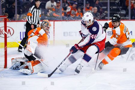 Columbus Blue Jackets' Dean Kukan, center, shot goes wide on Philadelphia Flyers' Brian Elliott, left, with Shayne Gostisbehere, right, trailing during the first period of an NHL hockey game, in Philadelphia