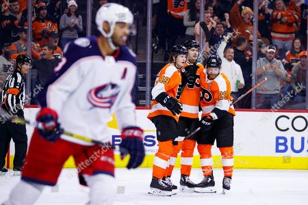 Philadelphia Flyers' James van Riemsdyk, center right, celebrates his power play goal with teammates as Columbus Blue Jackets' Seth Jones, left, skates by during the second period of an NHL hockey game, in Philadelphia