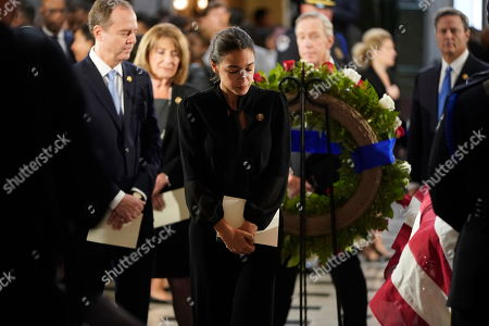 United States Representative Alexandria Ocasio-Cortez (Democrat of New York) and US Representative Adam Schiff (Democrat of California), Chairman, US House Permanent Select Committee on Intelligence, visit the flag-draped casket of US Representative Elijah Cummings (Democrat of Maryland) after a memorial service in Statuary Hall of the U.S. Capitol on Capitol Hill in Washington, DC,.