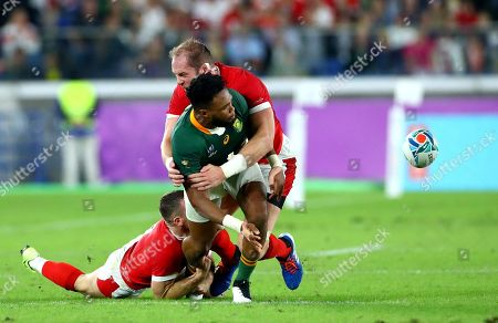 South Africa vs Wales. South Africa's Lukhanyo Am offloads while tackled by Wales' Gareth Davies and Alun Wyn Jones