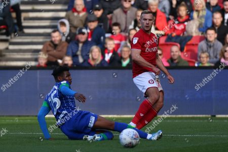 Bristol City's Andi Weimann challenged by Dujon Sterling (15) of Wigan Athletic during the EFL Sky Bet Championship match between Bristol City and Wigan Athletic at Ashton Gate, Bristol