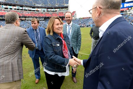 Tennessee Titans owner Amy Adams Strunk, center, talks with people on the field before an NFL football game between the Titans and the Tampa Bay Buccaneers, in Nashville, Tenn