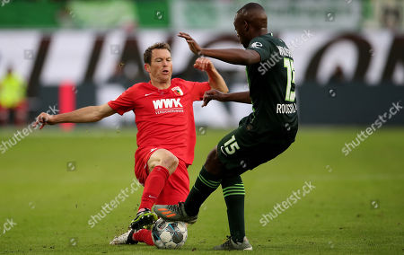 Augsburg's Stephan Lichtsteiner (L) in action with Wolfsburg's Jerome Roussillon (R) during the German Bundesliga soccer match between VfL Wolfsburg and FC Augsburg in Wolfsburg, Germany, 27 October 2019.