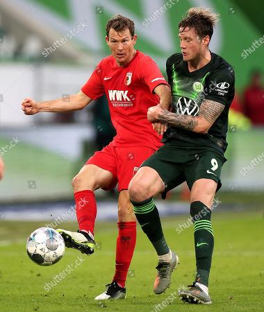 Augsburg's Stephan Lichtsteiner (L) in action with Wolfsburg's Wout Weghorst (R) during the German Bundesliga soccer match between VfL Wolfsburg and FC Augsburg in Wolfsburg, Germany, 27 October 2019.