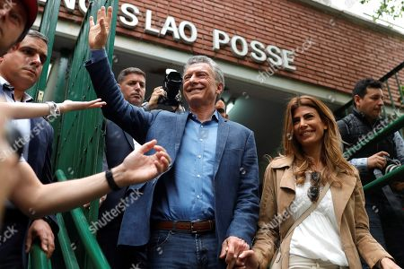 Argentina President Mauricio Macri (L) waves after voting next to his wife Juliana Awada in Buenos Aires, Argentina, 27 October 2019. Argentines have begun casting votes in presidential elections amid one of the worst economic crisis the country has ever seen. The country's 33.8 million eligible voters will decide either to stick with the status quo by re-electing Mauricio Macri or to return to Peronism with Alberto Fernandez.