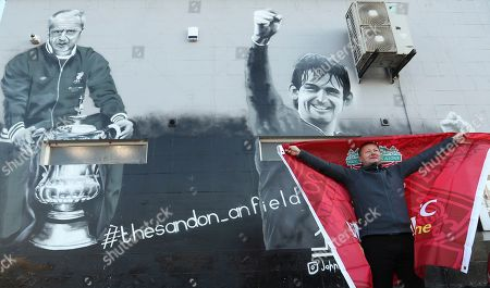A fan stands close a wall painted with a portrait of Liverpool's legends Bill Shankly, left, and Kenny Dalglish prior the English Premier League soccer match between Liverpool and Tottenham Hotspur at Anfield stadium in Liverpool, England