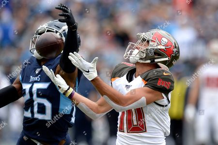 Tampa Bay Buccaneers wide receiver Scott Miller (10) catches a pass as he is defended by Tennessee Titans cornerback Logan Ryan (26) in the first half of an NFL football game, in Nashville, Tenn