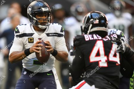 Seattle Seahawks quarterback Russell Wilson (3) works in the pocket as Atlanta Falcons defensive end Vic Beasley (44) pressures during the first half of an NFL football game, in Atlanta