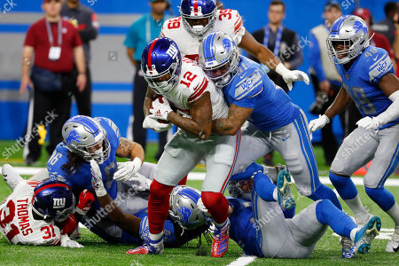 New York Giants wide receiver Cody Latimer (12) is stopped by Detroit Lions' Ty Johnson (31) during the second half of an NFL football game, in Detroit