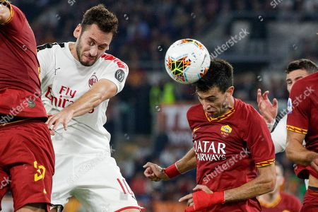 AC Milan's Hakan Calhanoglu, left, and Roma's Javier Pastore jump for the ball during a Serie A soccer match between Roma and AC Milan, at Rome's Olympic Stadium