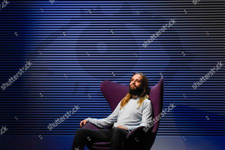 """A staff member poses with """"Big Brother Diary Room Chair, Series 1"""", 2000, courtesy Alan Davies and """"Big Brother Series 2 Logo"""", 2001, by Daniel Eatock."""