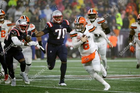 Cleveland Browns quarterback Baker Mayfield, right, runs from New England Patriots defensive back Terrence Brooks, left, and defensive tackle Adam Butler (70) in the second half of an NFL football game, in Foxborough, Mass
