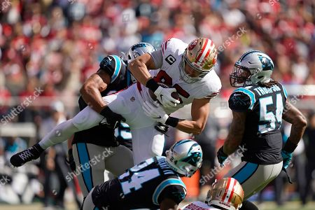 San Francisco 49ers tight end George Kittle is stopped with the ball by Carolina Panthers strong safety Eric Reidas as Panthers cornerback James Bradberry (24) and outside linebacker Shaq Thompson (54) look on during the first half of an NFL football game in Santa Clara, Calif
