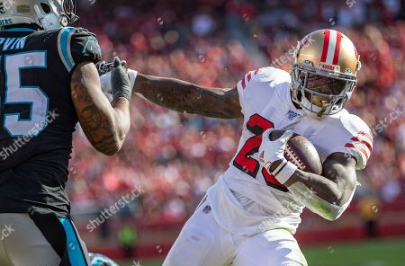 San Francisco 49ers running back Tevin Coleman (26) gives a stiff arm to Carolina Panthers linebacker Bruce Irvin (55) as he scores a touchdown, during a NFL game between the Carolina Panthers and the San Francisco 49ers at the Levi's Stadium in Santa Clara, California
