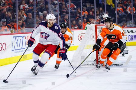 Columbus Blue Jackets' Alexander Wennberg, left, skates with the puck against Philadelphia Flyers' Shayne Gostisbehere, center, and Robert Hagg, right, during the first period of an NHL hockey game, in Philadelphia