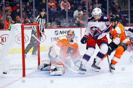 Columbus Blue Jackets' Dean Kukan, center, watches as his shot goes wide of Philadelphia Flyers' Brian Elliott, left, with Shayne Gostisbehere, right, defending during the first period of an NHL hockey game, in Philadelphia. The Flyers won 7-4