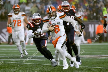 Cleveland Browns quarterback Baker Mayfield, center, runs from New England Patriots defensive back Terrence Brooks, left, and defensive tackle Adam Butler, right, in the second half of an NFL football game, in Foxborough, Mass