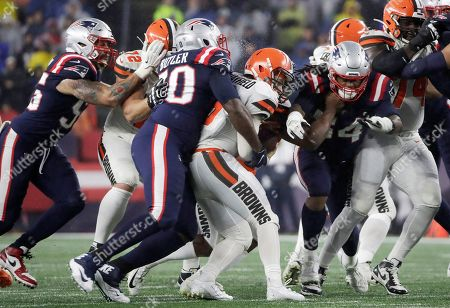 New England Patriots defensive tackle Adam Butler, second from left, sacks Cleveland Browns quarterback Baker Mayfield in the first half of an NFL football game, in Foxborough, Mass