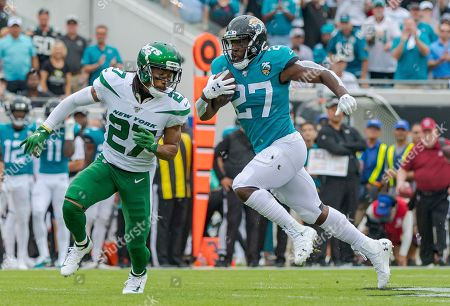 Stock Picture of Jacksonville, FL, U.S: New York cornerback Darryl Roberts (27) attempts to tackle Jacksonville running back Leonard Fournette (27)after breaking free for a 66 yard run during 1st half NFL football game between the New York Jets and the Jacksonville Jaguars at TIAA Bank Field in Jacksonville, Fl