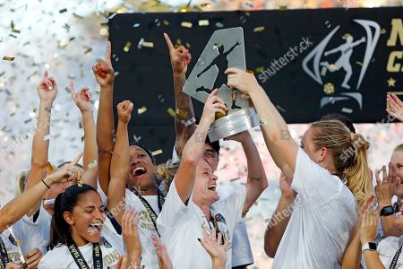 North Carolina Courage's Heather O'Reilly, center, holds the championship trophy following the team's win over the Chicago Red Stars in an NWSL championship soccer game in Cary, N.C