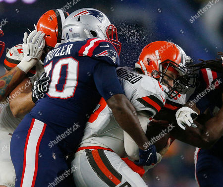 Stock Image of Cleveland Browns quarterback Baker Mayfield (R) is sacked by New England Patriots defensive tackle Adam Butler (L) during the second quarter at Gillette Stadium in Foxborough, Massachusetts, USA, 27 October 2019.