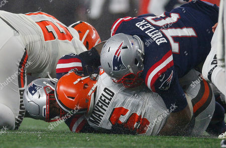 Stock Photo of Cleveland Browns quarterback Baker Mayfield (C) is sacked by New England Patriots linebacker Jamie Collins Sr. (L) and New England Patriots defensive tackle Adam Butler (R) during the fourth quarter o the New England Patriots win at Gillette Stadium in Foxborough, Massachusetts, USA, 27 October 2019.