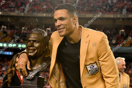 Kansas City Chiefs' former tight Tony Gonzalez poses with his statue after he was inducted in the Chiefs' Hall of Fame, during a ceremony at halftime of an NFL football game between the Kansas City Chiefs and the Green Bay Packers in Kansas City, Mo