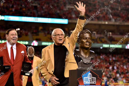 Former Kansas City Chiefs defensive back Johnny Robinson waves during his induction to the Kansas City Chiefs hall of fame, in a ceremony at halftime of an NFL football game between the Kansas City Chiefs and the Green Bay Packers in Kansas City, Mo