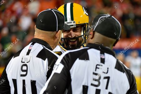 Green Bay Packers quarterback Aaron Rodgers jokes with line judge Mark Perlman (9) and field judge Mearl Robinson (31), before an NFL football game against the Kansas City Chiefs in Kansas City, Mo